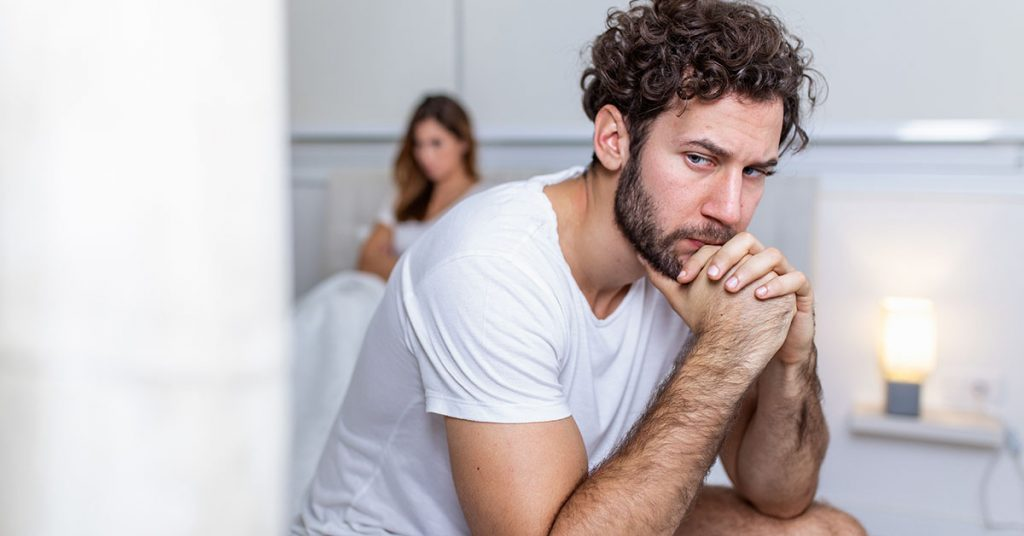 Sad thoughtful man after arguing with girlfriend.Relationship difficulties, conflict and family concept,unhappy couple having problems at bedroom. Sad guy sitting on bed,girlfriend in the background; blog: possible causes of erectile dysfunction