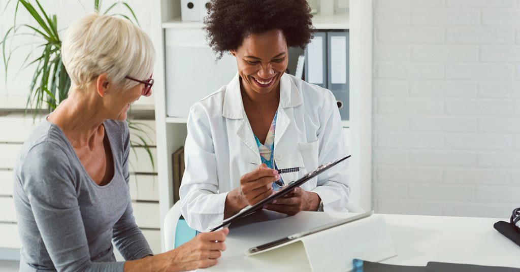 A female doctor sits at her desk and chats to an elderly female; blog: do women see urologists