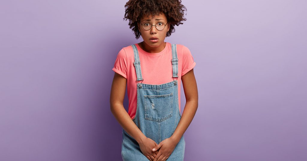 Dissatisfied girl keeps hands on crotch, presses lower abdomen, needs toilet badly, has syndrome of cystitis, wears spectacles, pink t shirt and denim sarafan, isolated on purple wall. Health problem; blog: Are There Different Types of Urinary Incontinence?