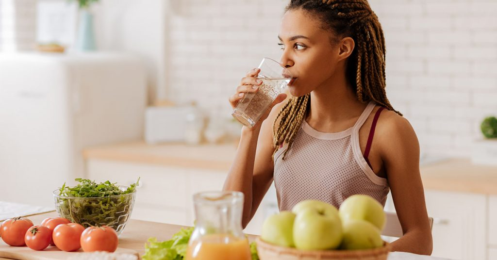 Water before breakfast. Slim and fit woman with many little braids drinking water before having breakfast; blog: Changing Your Diet to Prevent Kidney Stones