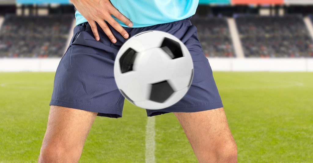 man playing soccer being hit by a soccer ball with force in the crotch when he misses a catch or as an unexpected accident on a clay court; blog: Preventing Testicular Trauma in Sports