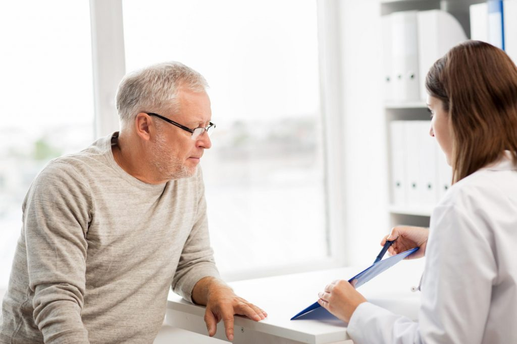 a doctor presenting the outline of a procedure to a male patient