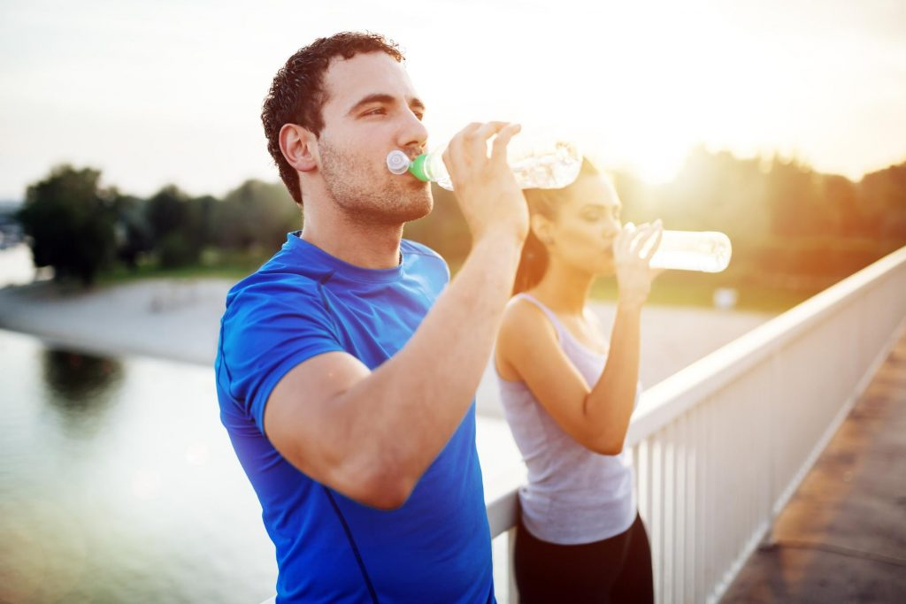 a man and a woman in athletic apparel drinking water bottles and staying hydrated